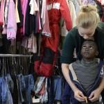 """Bir yardım görevlisi sığınmacı bir çocuğun kıyafet giymesine yardımcı oluyor. """"Bayernkaserne"""" denilen merkezde toplanan kıyafetler, ihtiyacı olan sığınmacılara dağıtılıyor. Fotoğrafçı: CHRISTOF STACHE Yer: Münih / Almanya Tarih: 9 Eylül 2015"""