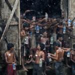 Denizde bir gemide bulunan Arakanlı Müslümanlar, yerleştirildikleri göçmen kampında, ellerindeki eşyalarla yağmur suyu toplamaya çalışıyor. Fotoğrafçı: YE AUNG THU  Yer: Myanmar Tarih: 4 Haziran 2015