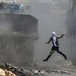 Filistinli protestocu içi boya dolu bir şişeyi, İsrail ordusuna ait dozere fırlatıyor. Fotoğrafçı: JAAFAR ASHTIYEH Yer: Batı Şeria Tarih: 21 Ağustos 2015