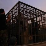 Bir kafese konulmuş Esad güçlerine bağlı askerler kamyonetlerle taşınıyor. Kafese konulan askerler, canlı kalkan olarak kullanılıyor. Fotoğrafçı: AHMAD AL-FAROQ Yer: Suriye Tarih: 31 Ekim 2015