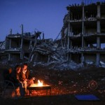 YPG ile IŞİD arasındaki çatışmalar sonucunda Kobani kenti adeta enkaza döndü. Bu enkazlar arasında iki kişi ısınmaya çalışıyor. Fotoğrafçı: YASİN AKGÜL Yer: Kobani / Suriye Tarih: 22 Mart 2015