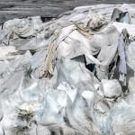 Kadın bir dağcı izolasyon köpükleriyle sarılmış bir buzulun yanında buz tırmanışı denemeleri yapıyor.  Fotoğrafçı: FABRICE COFFRINI Yer: İsviçre Tarih: 14 Temmuz 2015