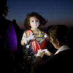 Türkiye'den Kos'a şişme bir botla geçen sığınmacılar arasındaki bir çocuğun can yeleği çıkartılıyor.  Fotoğrafçı: ANGELOS TZORTZINIS Yer: Kos / Yunanistan Tarih: 13 Ağustos 2015